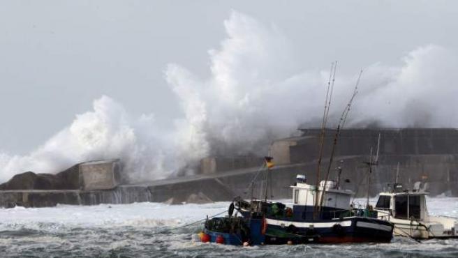 Grandes olas rompen un tramo del dique del puerto de Cudillero. Una borrasca mantiene en alerta a cuarenta provincias de quince comunidades.