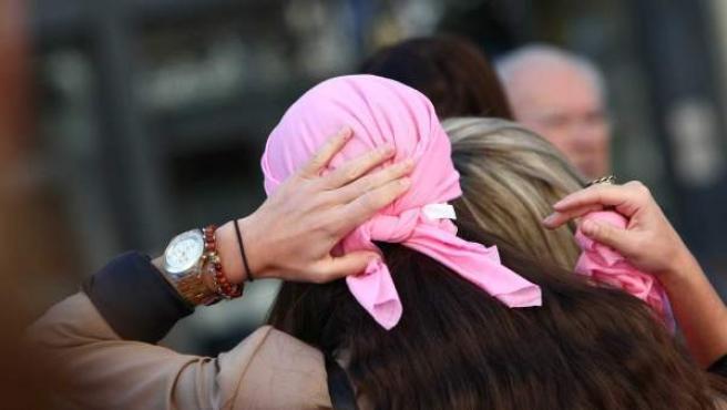 Una mujer con una pañoleta rosa, color representativo de la lucha contra el cáncer de mama.