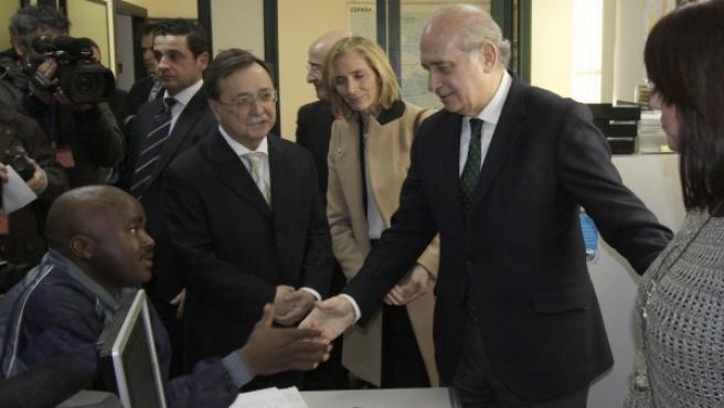 El ministro del Interior, Jorge Fernández Díaz (2d), junto al presidente de Ceuta, Juan José Vivas (2i), saluda a un inmigrante.