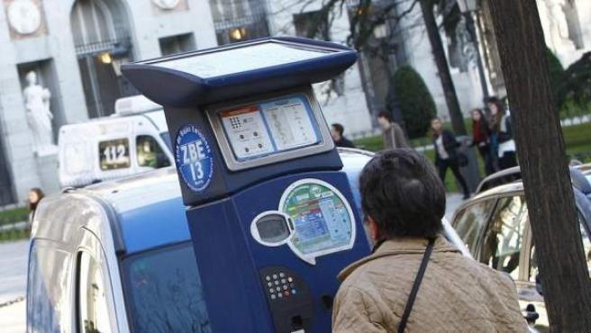 Una mujer saca un tique de un parquímetro en el Paseo del Prado, en Madrid.