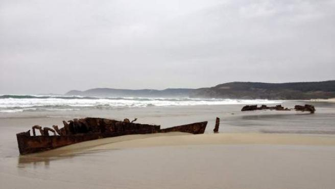 El temporal que ha azotado las costas gallegas ha dejado al descubierto en la playa coruñesa de Fisterra un barco hundido desde el año 1927.