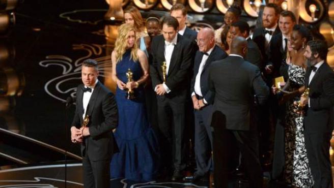 Brad Pitt, a la izquierda de la imagen, productor de 12 años de esclavitud, recoge el Oscar que reconoce a la cinta como la mejor película del año. La 86 edición de los Oscar también estuvo marcada por el histórico triunfo del mexicano Alfonso Cuarón, el primer latino en ganar el premio al mejor director.
