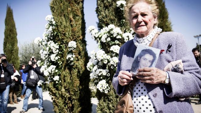 Una mujer sostiene una foto de una de las víctimas durante el homenaje, en el Bosque del Recuerdo del parque del Retiro, a los 191 fallecidos en los atentados del 11M.