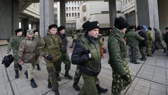 Varios cosacos que llevan el gorro tradicional de piel hacen guardia a las afueras del edificio del Parlamento regional en Simferópol, Crimea.