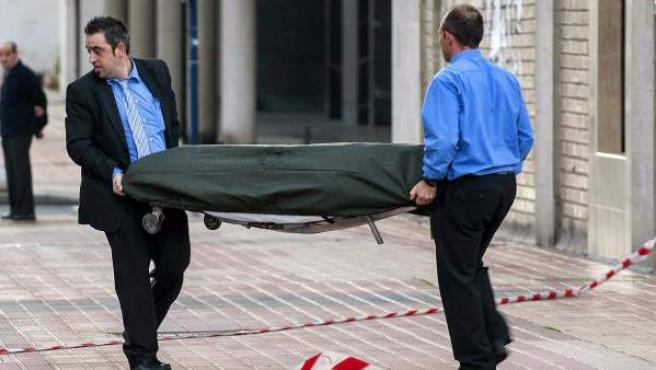 Trabajadores de la funeraria trasladan el cadáver de una mujer, de 53 años, que se suicidó en Barakaldo cuando iba a ser desahuciada.