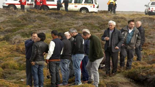 Amigos y familiares de los pescadores desaparecidos observan desde la costa, a pesar de la niebla, los trabajos de los equipos de rescate.