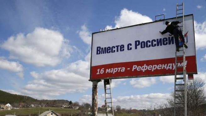 """Un trabajador coloca un cartel en el que se lee: """"Juntos con Rusia, 16 de marzo- referéndum"""", a las afueras de Simferopol, Crimea."""