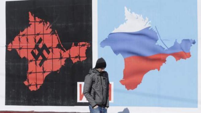 Un viandante pasa por delante de un cartel que anima a la población a votar en el referéndum sobre Crimea, en Sebastopol (Ucrania).