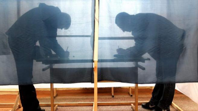 Dos ciudadanos crimeos marcando una de las dos respuestas posibles en el referéndum de Crimea sobre la anexión a Rusia en un colegio electoral en Simferopol, Crimea.