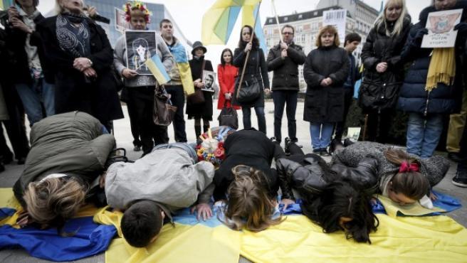 La cantante y activista ucraniana Ruslana Lyzhychko (delante, 2-d) y otros activistas pro-ucranianos besan una bandera de Ucrania durante una protesta delante de la sede de la Unión Europea, en Bruselas (Bélgica).