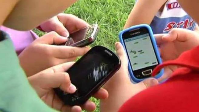 Niños usando móviles.
