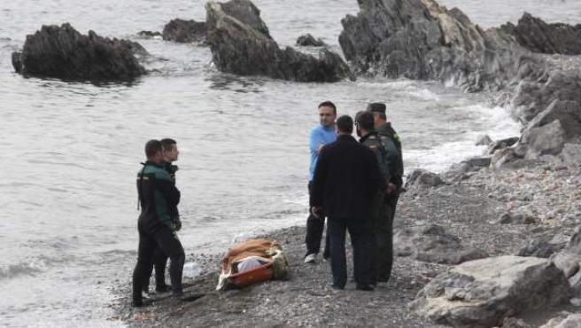 Miembros de la Guardia Civil junto a un cadáver de un inmigrante hallado en la playa de la Ribera, en Ceuta.