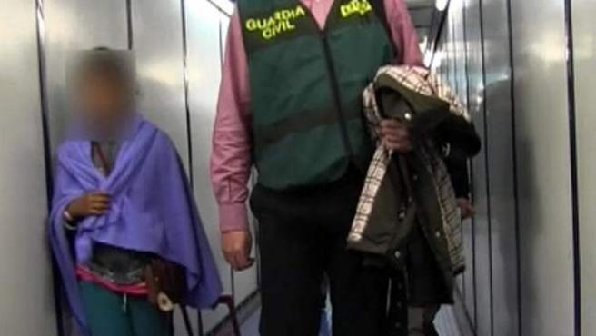 Fotografía facilitada por la Guardia Civil de la niña (i) de 9 años secuestrada en Bolivia durante siete meses, a su llegada al aeropuerto de Barajas, procedente del país andino, donde ha hecho escala para coger un nuevo avión que la ha dejado en el aeropuerto de El Prat a las 09.30 horas.