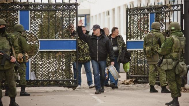 Un militar de la Armada ucraniana en Crimea (c) abandona su cuartel general escoltado por soldados de las fuerzas rusas de autodefensa, en la ciudad de Sebastopol.