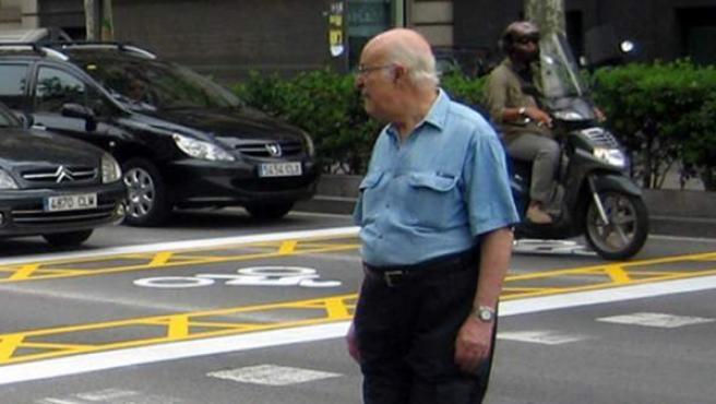 Una persona d'edat avançada creuant la Gran Via de Barcelona.