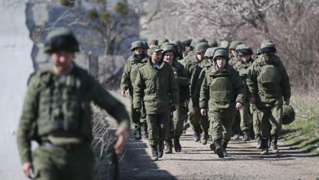 Soldados rusos vigilan el territorio de la unidad militar ucraniana en Perevalnoye que ha sido tomada por los rusos a las afueras de Simferópol hoy, viernes 21 de marzo de 2014.