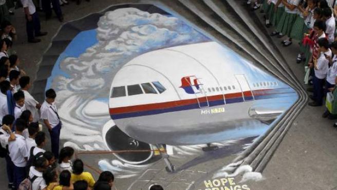 Artistas del grupo artístico Guhit Visual Arts muestran una imagen del avión de Malaysia Airlines desaparecido en el patio del instituto Benigno Ninoy Aquino en Makati al sur de Manila (Filipinas).