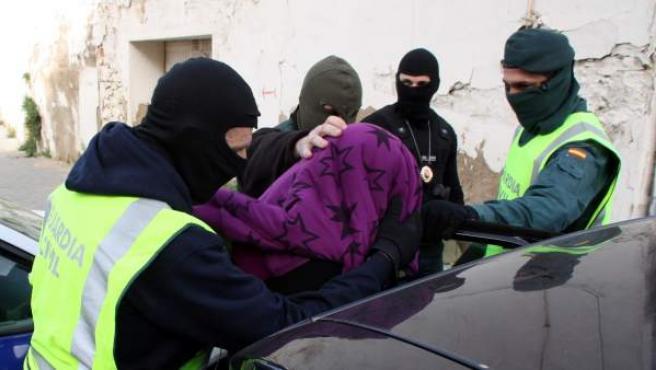 Varios agentes de la Guardia Civil introducen en un coche policial a uno de los ocho detenidos en Tarragona y Reus durante una macrooperación contra la banda de los Trinitarios.