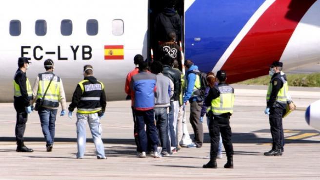 Agentes de la Policía Nacional trasladan hasta el avión a un grupo de inmigrantes, todos ellos de origen subsahariano, que ha salido vía aérea desde Melilla a centros de la península.