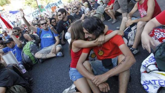 Dos jóvenes 'indignados' se abrazan durante una sentada.