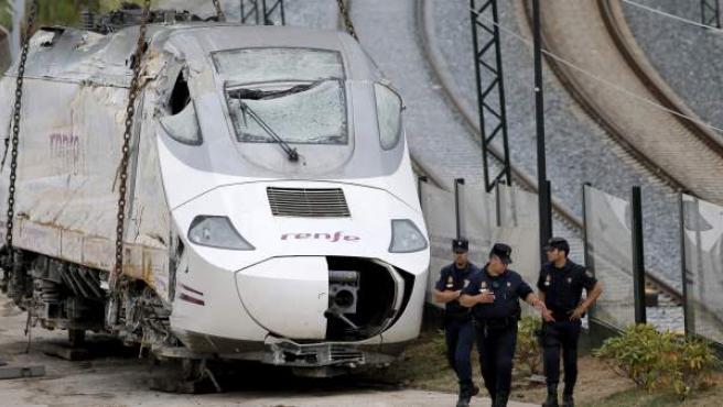 Efectivos de la policía custodian la locomotora del tren Alvia que descarriló en las inmediaciones de Santiago.