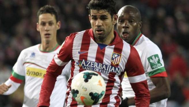 El delantero del Atlético de Madrid Diego Costa (c) escapa de dos jugadores del Granada, durante el partido de Liga en Primera División.