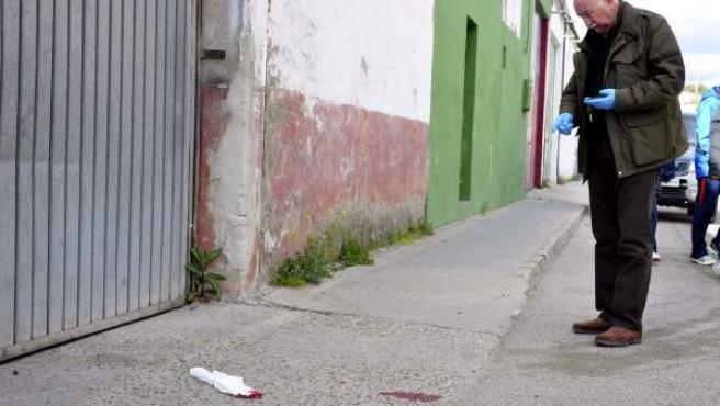 Un miembro de la Policía Judicial señala el lugar en el que una mujer ha resultado herida grave al recibir un tiro en la cabeza cerca de un parque público de Medina del Campo (Valladolid).