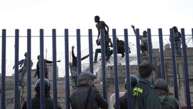 Inmigrantes encaramados a la valla fronteriza en Melilla.