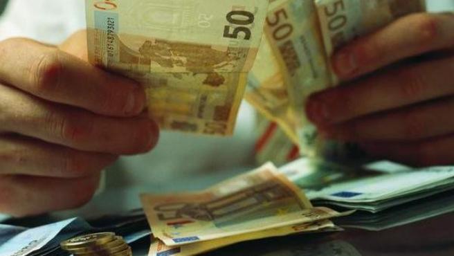 Un empresario pagando en metálico.