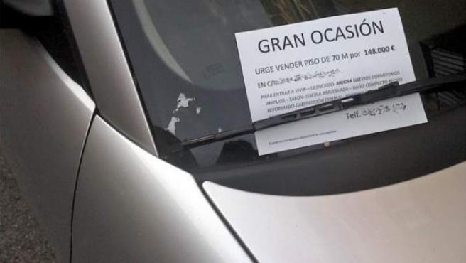 El anuncio de un piso en venta bajo el parabrisas de un coche.