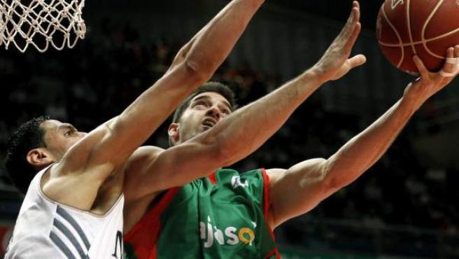 El jugador tunecino del Real Madrid Salah Mejri (i) intenta taponar a Marcos Mata, del Cajasol, durante el partido correspondiente a la jornada 26 de la fase regular de la Liga ACB.