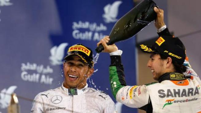Sergio Pérez derrama champagne (sin alcohol) sobre Lewis Hamilton en el podio del GP de Baréin de Fórmula 1.