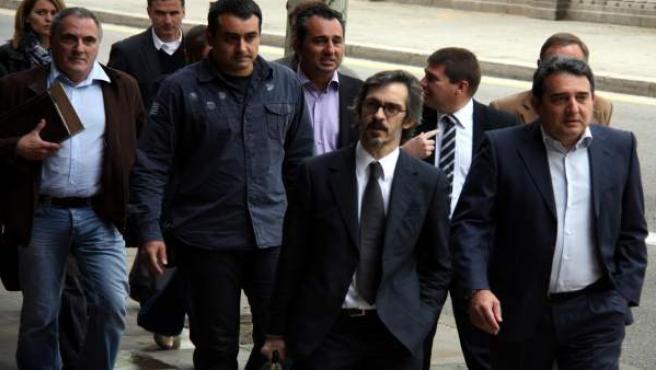 El exalcalde de Sabadell, Manel Bustos (derecha), a su llegada al Palacio de Justicia acompañado de su abogado, Cristóbal Martell, su hermano Francisco (detrás) y varios concejales.