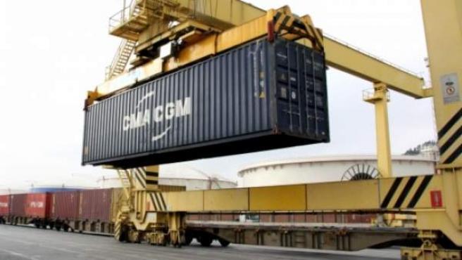 Una grúa coloca un contenedor sobre un tren de mercancías en el Puerto de Barcelona.