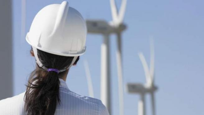Una trabajadora observa un aerogenerador.