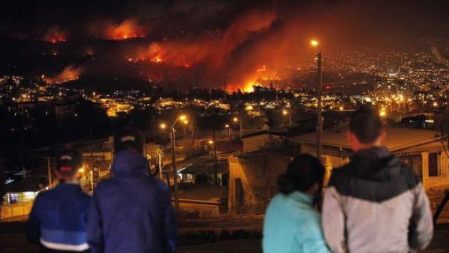 Cuatro personas observan cómo un incendio forestal arrasa con zonas urbanas en la ciudad de Valparaíso, Chile.