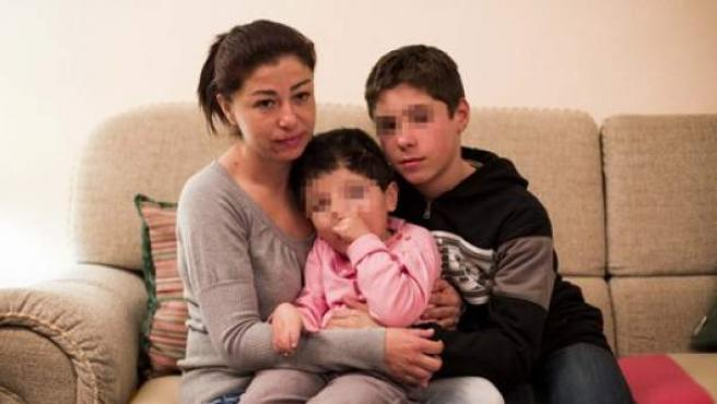 Carmina, a la derecha, abrazando a la pequeña Sonia junto a su hermano mayor.