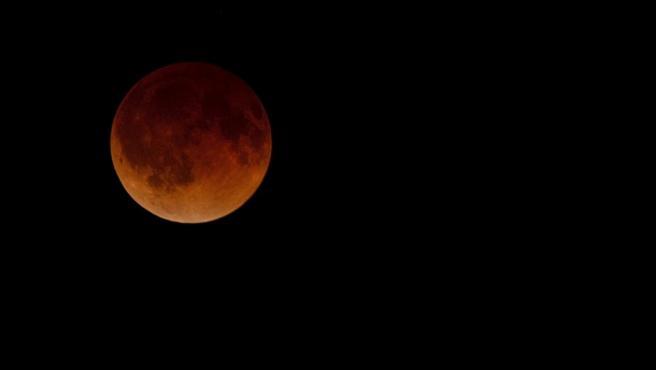La Luna se tiñe de rojo y naranja durante ek eclipse lunar total visto desde Wichita, Kansas (Estados Unidos). El eclipse total de Luna es un fenómeno que se produce cada diez años aproximadamente y que hace que veamos el satélite de color rojo.