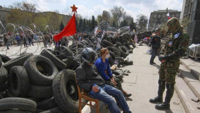 Manifestantes prorrusos permanecen sentados junto a una barricada frente a un edificio ocupado de la administración regional de Donetsk.