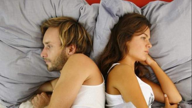 Una pareja en la cama, dándose la espalda.