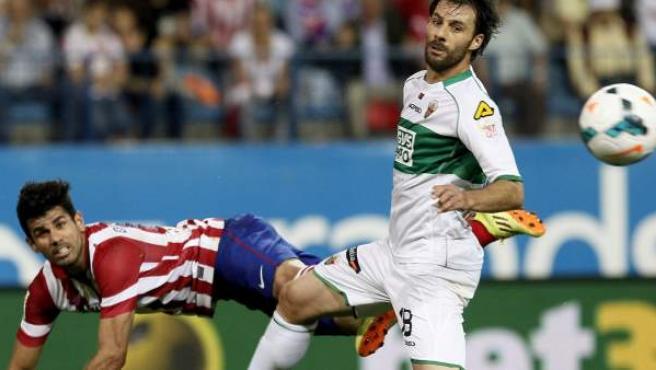 El delantero del Atlético de Madrid Diego Costa (i) y el defensa del Elche Sergio Pelegrín, durante el partido de la jornada 34 de liga en Primera.