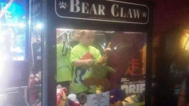 Imagen captada por la cadena estadounidense KETV en la que un niño de tres años se ve en una máquina expendedora.