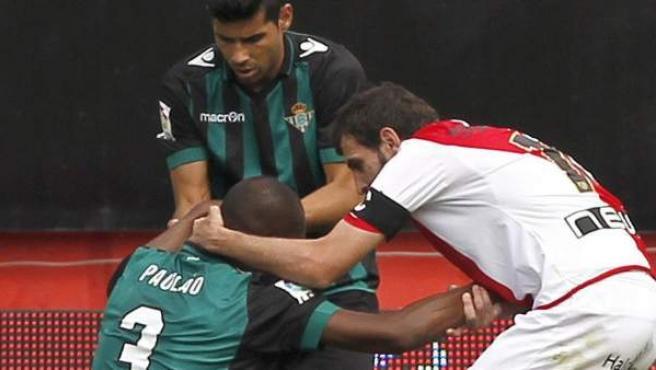 El medio del Rayo Vallecano Roberto Trashorras (d) intenta consolar al defensa brasileño del Real Betis Paulão Santos, que pidió el cambio tras meter un gol en propia puerta.