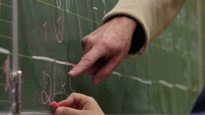 Un maestro enseña matemáticas a un niño en la pizarra.