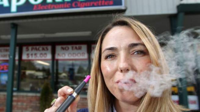 Una mujer fuma con un cigarrillo electrónico.