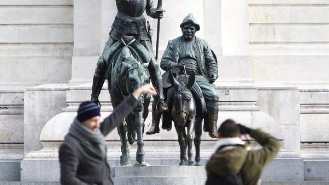 Dos turistas fotografían la estatua de Don Quijote y Sancho Panza, en la Plaza de España de Madrid.
