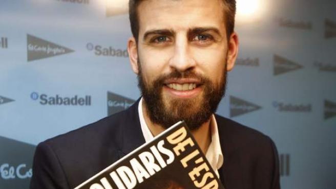El defensa del Fc Barcelona, Gerard Pique, posa con el libro de historias solidarias escrito por periodistas deportivos y prologado por él jugador barcelonista.