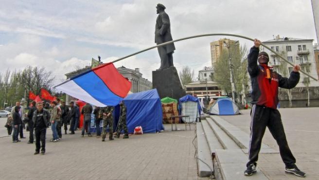 Un manifestante prorruso ondea una bandera rusa junto al monumento a Lenin en Donetsk.