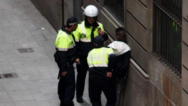 Varios agentes detienen a un carterista en plena calle.