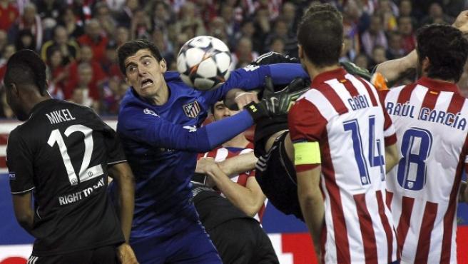 El portero belga del Atlético de Madrid Thibaut Courtois (2i) intenta atrapar el balón entre sus compañeros Gabi (2d) y Raúl García (d) y el centrocampista Obi Mikel (i), del Chelsea.